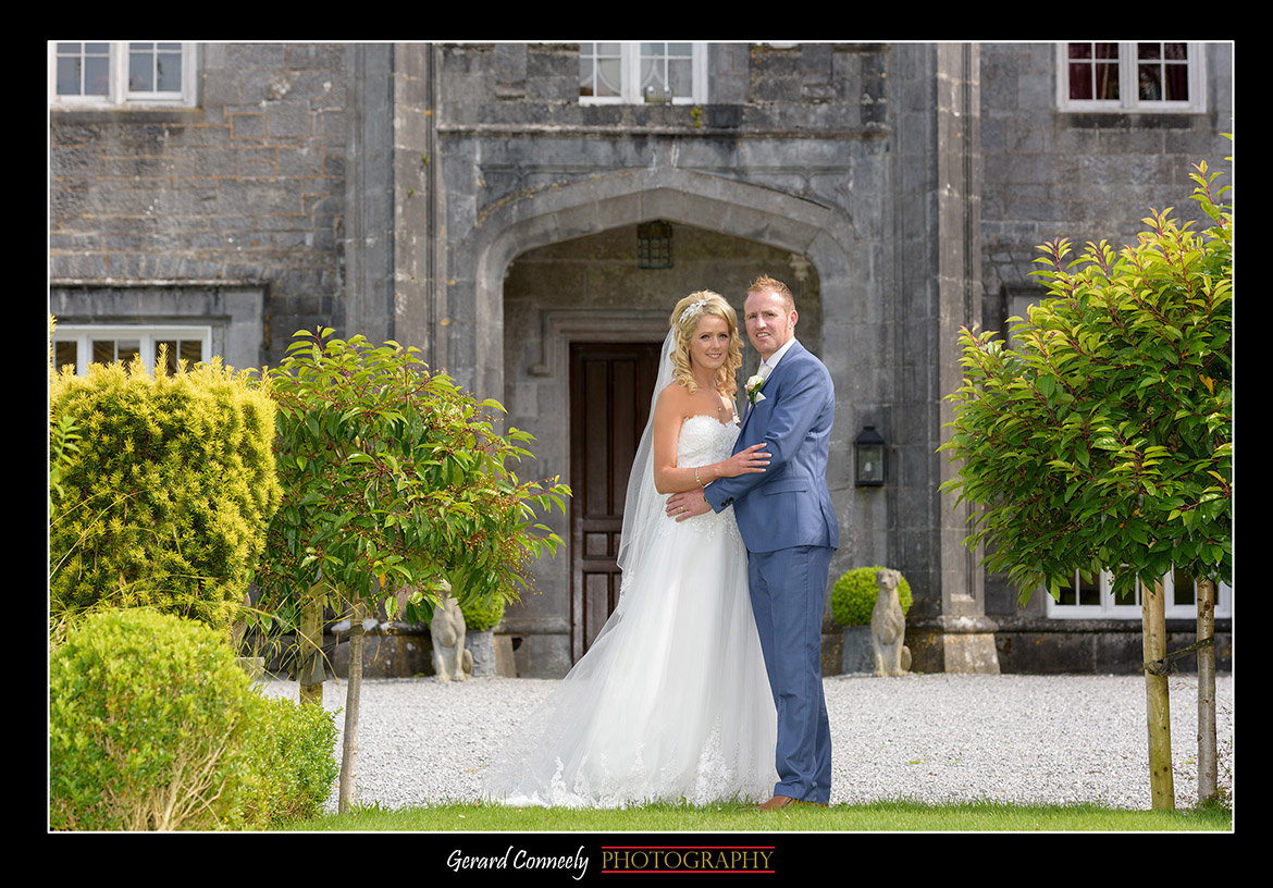 bride and groom at front of lough cutra castle on their wedding by gerard conneely photography