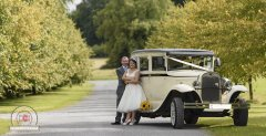 wedding photo of bride and groom next to wedding car Galway